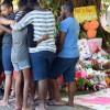 Un grupo de personas se consuelan mutuamente, mientras asisten a una ofrenda floral cerca de la casa en la que ocho niños fueron apuñalados hasta la muerte en el suburbio de Cairns Manoora, Australia. EFE