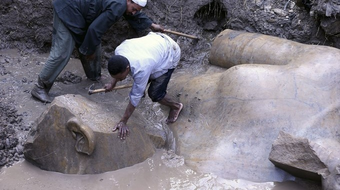Varios trabajadores egipcios preparan la retirada de varias partes de una estatua para su restauración tras ser desenterradas en el barrio de Souq al Khamis, en El Cairo (Egipto). EFE