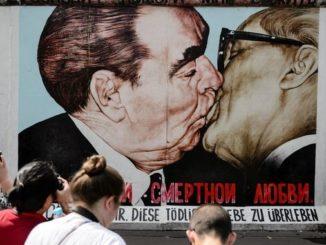 """Varios turistas fotografían el mural """"Beso fraternal"""" del artista ruso Dmitri Vrúbel en el muro de Berlín (Alemania). El mural del beso entre los líderes soviético y de la Alemania comunista, realizado en 1990 en el muro de Berlín marcó el final de una era. EFE/Archivo"""