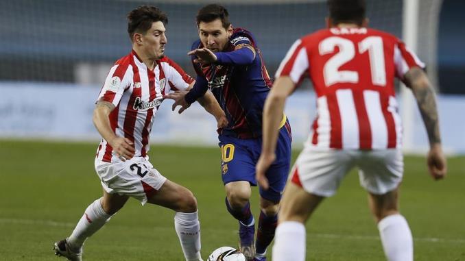 El delantero argentino del FC Barcelona, Leo Messi (c), intenta llevarse el balón ante el centrocampista del Ahtletic, Unai Vencedor, durante el encuentro correspondiente a la final de la Supercopa de España que disputaron en el estadio de la Cartuja de Sevilla. EFE/Jose Manuel Vidal.